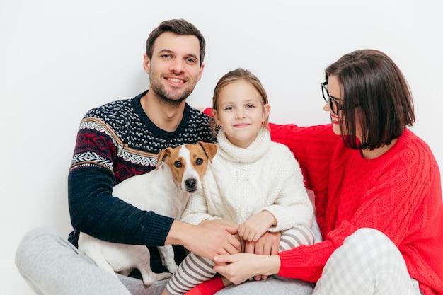Счастливая семья из трех членов семьи и собаки, обнимаются и счастливо улыбаются