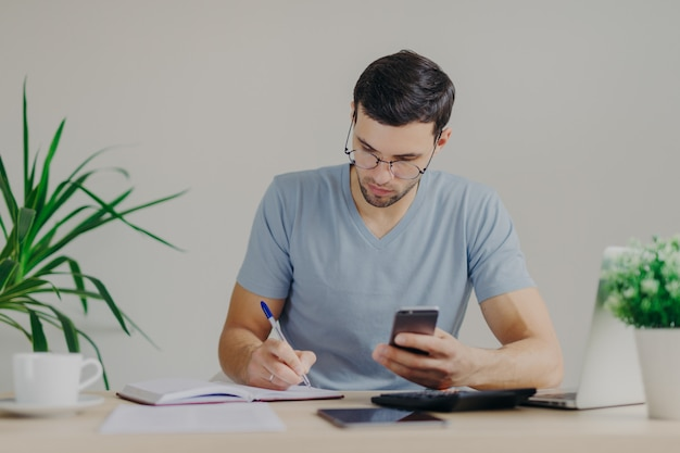 集中した若い男性会計士はノートに書いて、ビジネス分析を行います