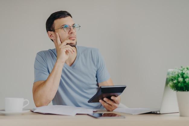 深刻な物思いにふける男性は丸いメガネを着用し、一般的なラップトップコンピューターと電卓を使用して広がりを計算します