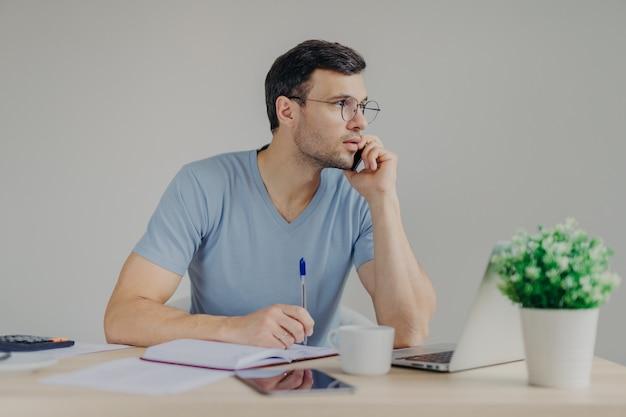 深刻な男性の財務マネージャーは携帯電話で話し、パートナーとの問題を解決し、日記にメモを書きます