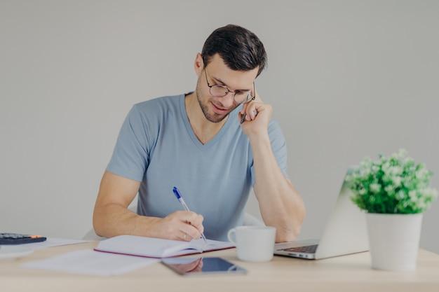 深刻な黒髪の若い男性が開いたラップトップの前に座って、携帯電話で話し、メモを書き留めます