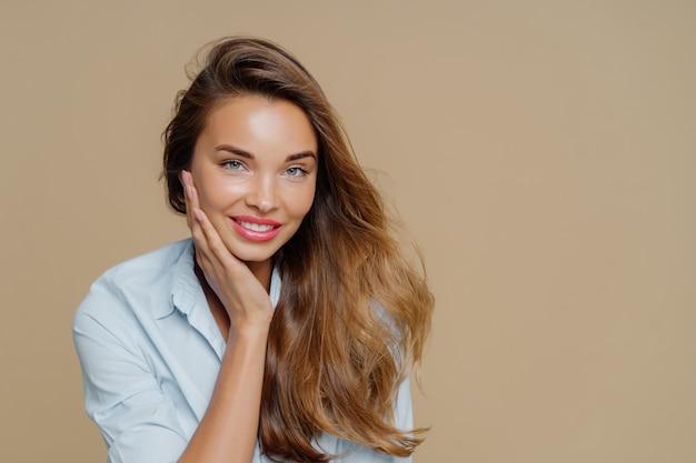 Веселая улыбающаяся женщина касается щеки, имеет зубастую очаровательную улыбку, носит рубашку, смотрит на камеру