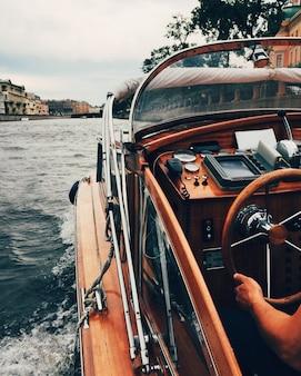モーターボートからの眺め。認識できない男が川で魚雷艇を運転