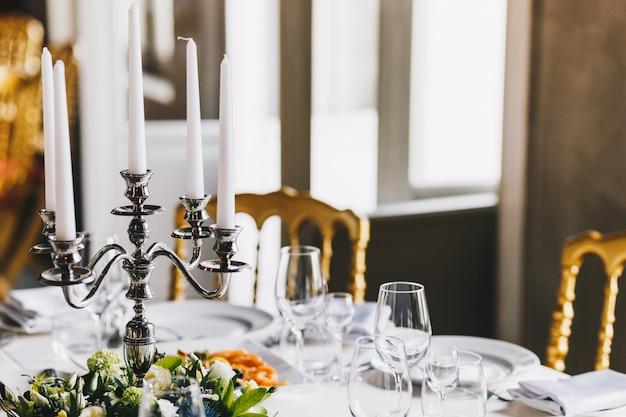 キャンドルスティックと白いキャンドル、居心地の良いレトロなレストランの豪華な食器でお祝いの装飾が施されたテーブル