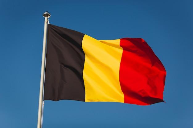 Флаг бельгии на мачте. национальный флаг против голубого неба ветра. флаг бельгии, столицы брюсселя