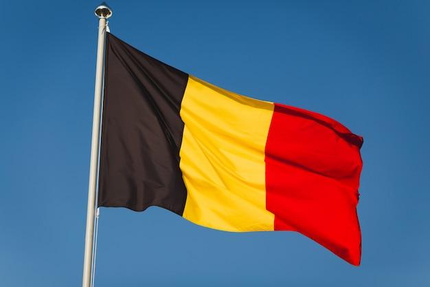 Национальный флаг бельгии на флагштоке перед голубым небом. черный, желтый и красный цвета