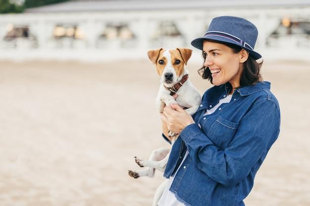 女の子は彼女の腕の中で犬を保持します