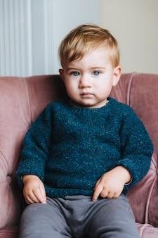 明るい髪と青い目を持つかわいい小さな子供は、セーターとズボンを着ています。