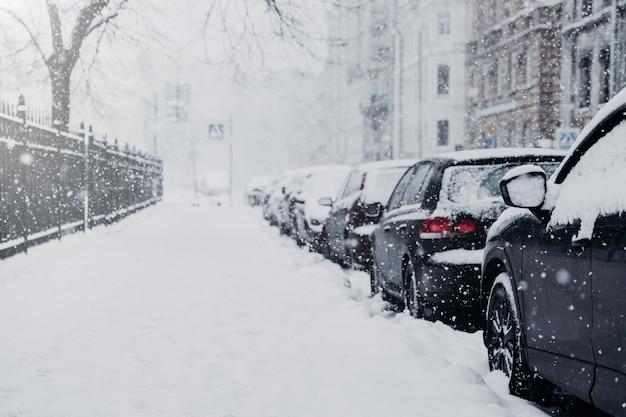 雪の中で美しい街。雪で覆われた車は駐車場に立つ。大雪または吹雪
