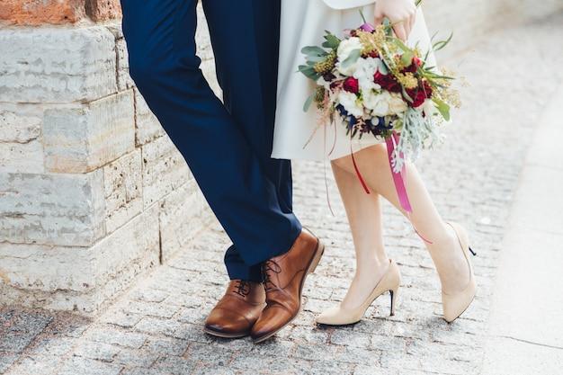 かかとの高い白い靴の美しい花嫁のショットをトリミングは、正式なお祝いスーツを着ている新郎の近くに素敵なブーケスタンドを保持します