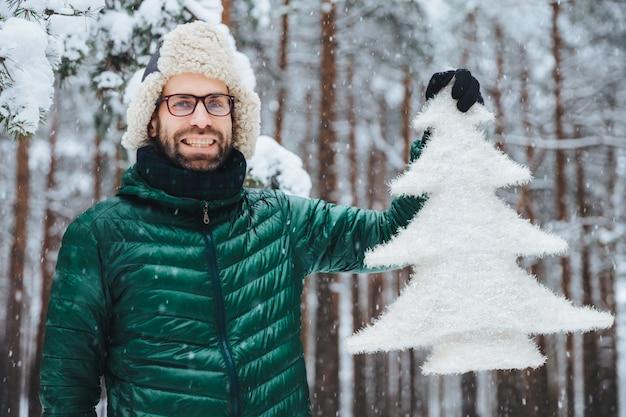 未熟な中年男性の耳の暖かい帽子と緑のアノラックを笑顔