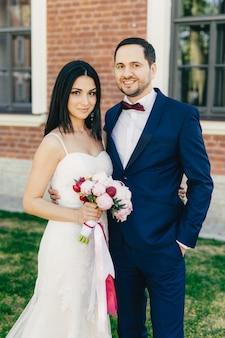 ちょうど結婚したカップルがお互いを受け入れ、幸せな表情を持ち、お互いに近くに立っている