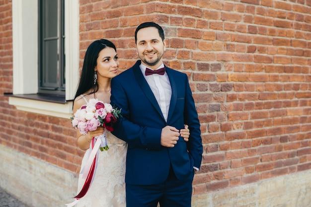 写真を撮るためにポーズをとってロマンチックな若い素敵な夫婦は、幸せな楽しい表情を持っています