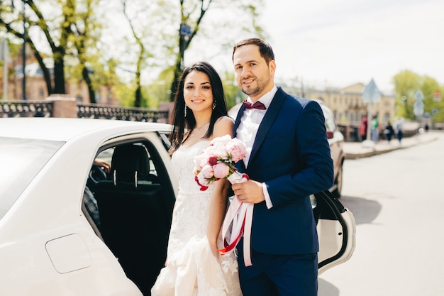 素敵な結婚されていたカップルが車の近くに隣同士に立っています。