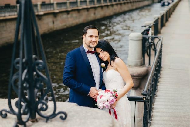 愛情のこもった愛情のあるカップルは彼らの結婚式を祝う、橋と川の近くのスタンドとしてカメラにポーズをとる