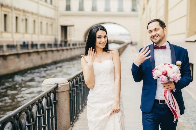 Восхитительные молодожены показывают кольца на пальцах, радуясь свадьбе