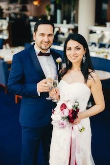 シャンパンのグラスを持った新郎新婦、結婚式を祝い、お祝いホールでゲストを待ち、顔に心地よい笑顔を