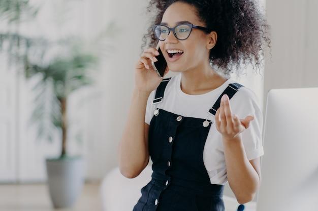 Обрезанное изображение счастливого кудрявого подростка активно обсуждает что-то по мобильному телефону