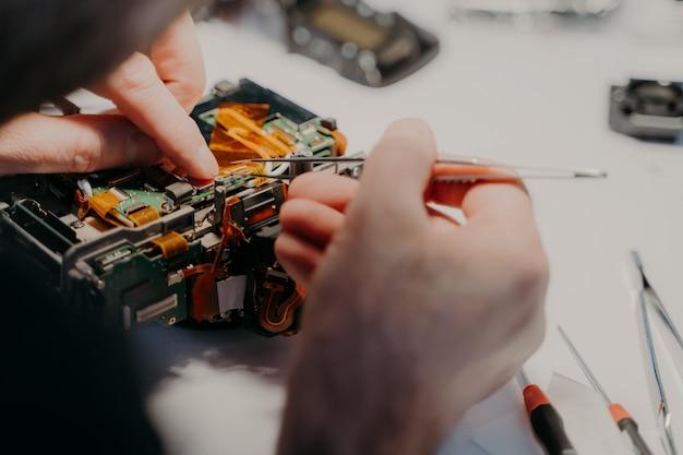 プロの技術者がカメラの分解部品の修理、ピンセットの保持、サービスセンターでの作業を行います。