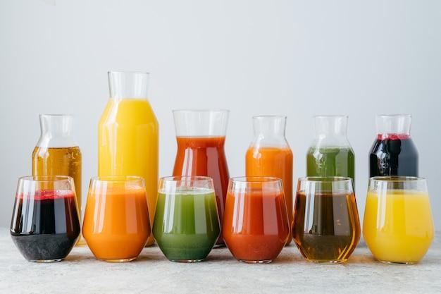 白い背景で隔離されたガラスの瓶に色とりどりのフルーツジュース。