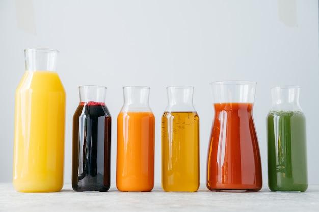 白い背景の上の行に立っている新鮮な色とりどりの飲み物のガラス瓶。