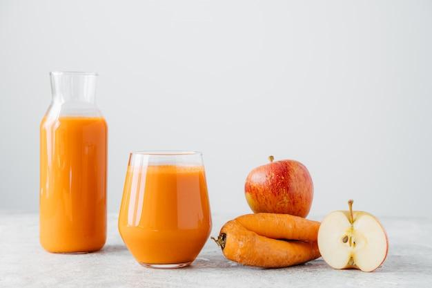 ニンジンとリンゴの白い背景で隔離のオレンジジュースのグラス