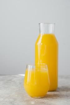 ビタミンがたっぷり入ったガラス製品で満たされた冷たい新鮮なオレンジジュース