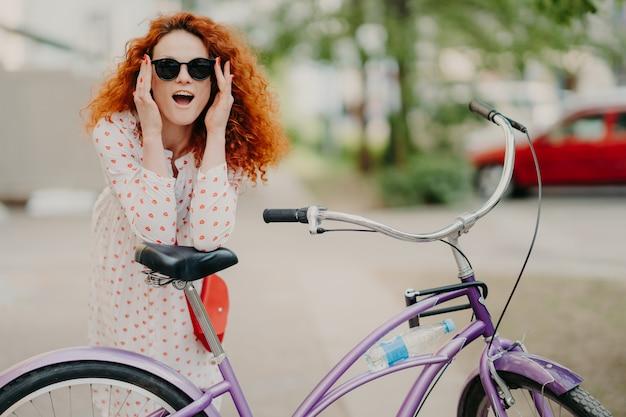 Счастливая женщина с вьющимися лисьими волосами, опирается на седло своего велосипеда,