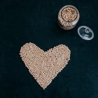 Сухой чистый нут в стеклянной банке. сердце из органического сырого гарбанзо. черный фон. растительный белок. фасоль для приготовления полезного блюда
