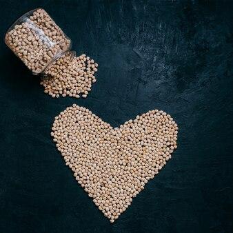 Здоровая сушеная гарбанзо или нут, вылитые из стеклянной банки, в форме сердца, органические сырые бобы