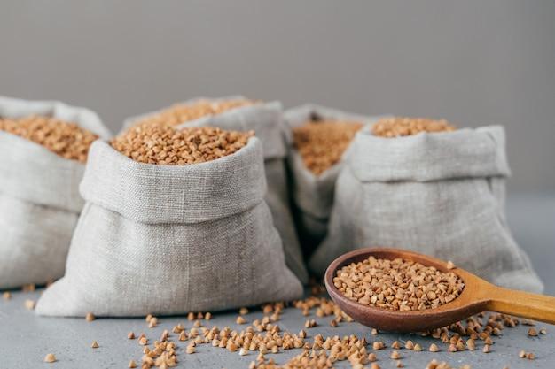 ダイエットと栄養の概念。灰色の背景に分離された袋で収穫された茶色のそば。調理用の乾燥シリアル