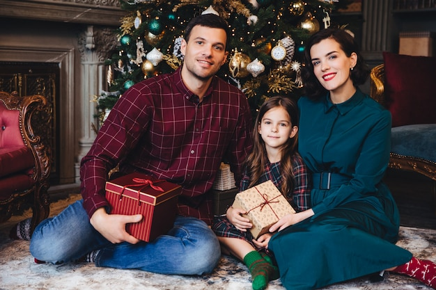 父、母と娘は一緒に休日を楽しんで、飾られた新年の木の近くのリビングルームに座って喜んで笑顔