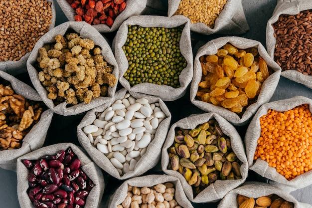 Цветастые различные фасоли в мешках ткани. сырые ассорти из бобовых. шелковица, гречка, фисташки, изюм, миндаль, гарбанзо и другие. здоровые злаки.
