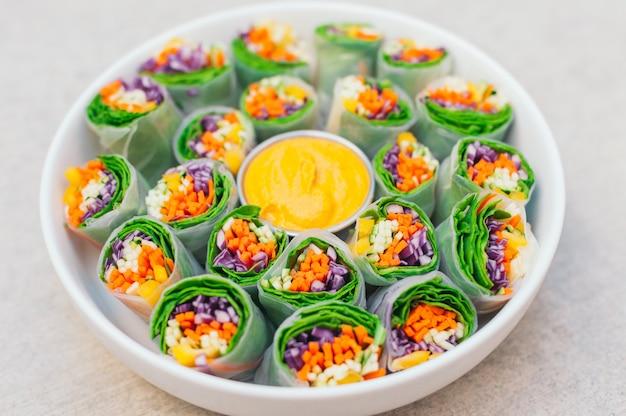 Вкусные зеленые блинчики с начинкой из рисовой бумаги и шпината, заправленные свежими нарезанными овощами. маленькая тарелка с желтым соусом карри в середине
