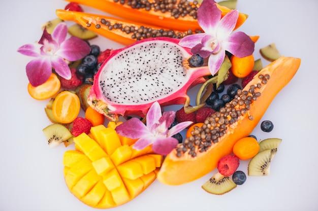 Спелые фрукты даргон, папайя, киви, манго с кумкватом, украшенные красивыми орхидеями.