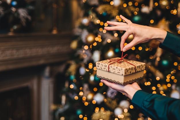 Удивление и приятные моменты. женщина оборачивает новогодний подарок как стоит в гостиной возле красиво украшенной елки