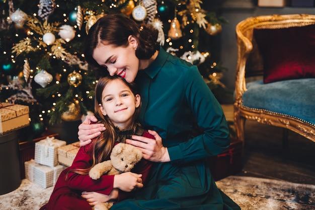 母は、飾られたクリスマスツリーの近くに一緒に座ると彼女の小さな娘を抱きしめます