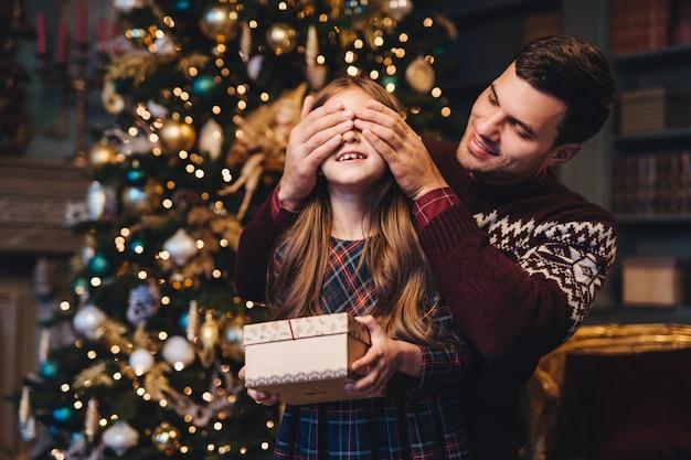 若い父親の肖像画は娘の目を覆い、彼女を驚かせ、プレゼントを贈り、クリスマスツリーの近くに立つ