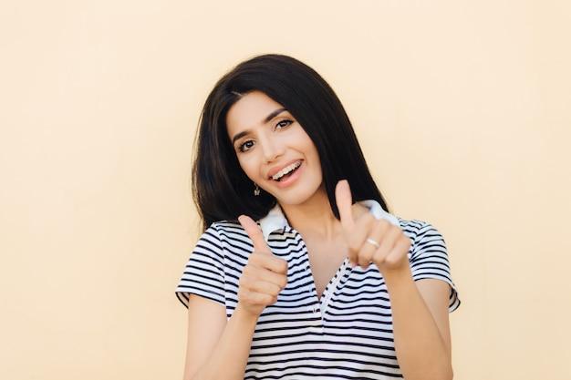喜んで若い女性の女性が親指を立て続け、何かを承認する