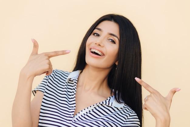 Портрет счастливой великолепной женской модели показывает пальцами на лицо
