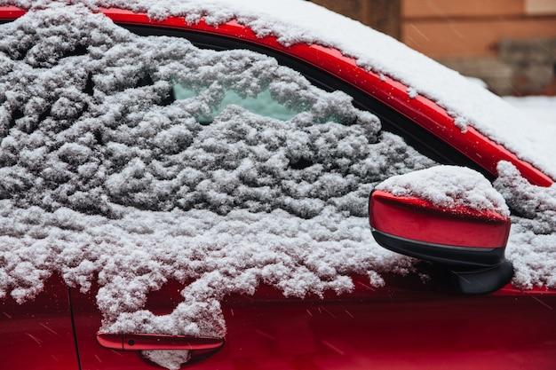 Красная машина покрыта густым снегом. зимняя метель и плохие погодные условия