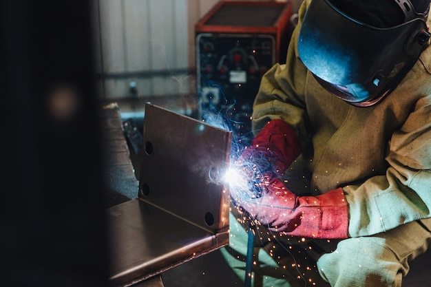 Концепция сварки. промышленный рабочий или сварщик носит защитную маску и перчатки, возводит техническую сталь на заводе