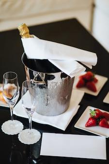 Бутылка шампанского в ведре со льдом и пустые бокалы на черном столе с вкусной клубникой