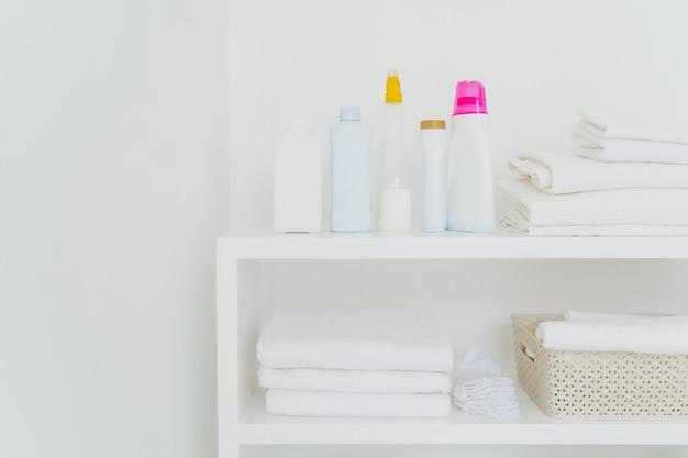 分離されたコンソール上の洗剤ときれいな白いタオルのスタック。バスルームでの新鮮な洗濯と液体洗浄