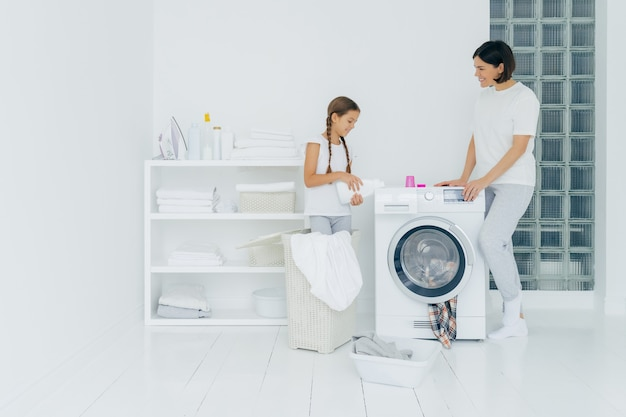 幸せな母と娘の屋内ショットは洗濯機の近くに立ち、女の子は液体の粉を注ぎ、汚れた服を洗濯機に入れ、家事をし、家で洗濯の日を過ごします。家事のコンセプト