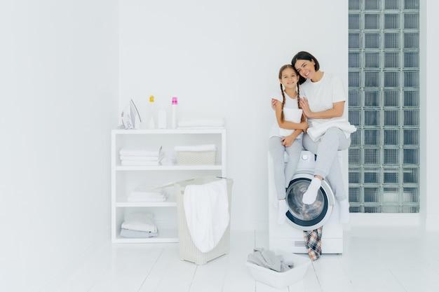美しい女性と彼の小さな娘のショットは抱擁し、快適に笑顔、洗濯機に座って、洗濯室でリネンを洗い、友好関係を持ち、自宅で洗濯をします。家事コンセプト