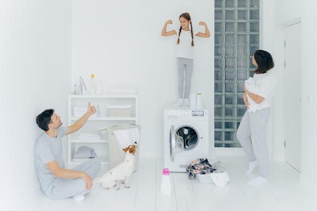 Изображение радостного маленького ребенка поднимает руки, показывает бицепс и стену, отец показывает как знак большим пальцем вверх, стоит в стиральной комнате с кучей одежды в тазике возле стиральной машины, моющего средства. молодец работа