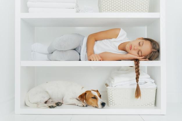 Спящая маленькая девочка лежит на белой полке