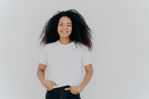 Молодая афроамериканка носит белую футболку, выражает хорошие эмоции