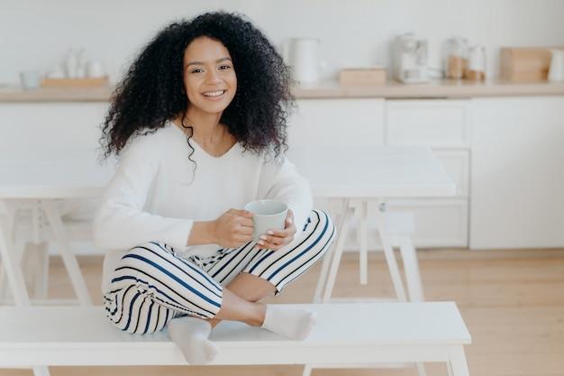 白いベンチでロータスポーズで座っている陽気な巻き毛のアフリカ系アメリカ人の女性は、おいしい香り豊かな飲み物を一口